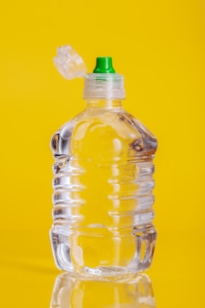 Plastic bottle of mineral water on a bright yellow background