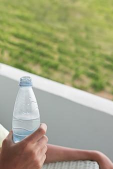 Пластиковая бутылка воды в руке. парень на балконе пьет воду