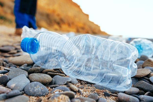 ビーチに残されたペットボトルのゴミをクローズアップ