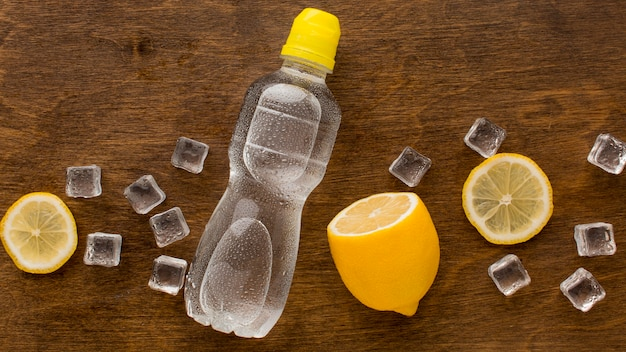 Plastic bottle of water and lemon top view