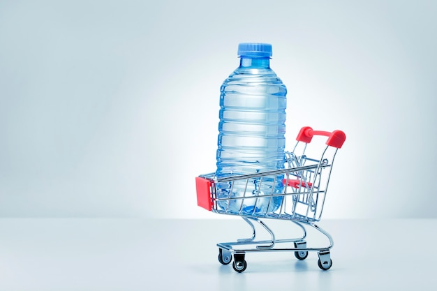 Plastic bottle of water in trolley on grey background with copy space.