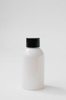 ボディケア化粧品や白いテーブルの上の髪のための黒い帽子のプラスチックボトル。側面図