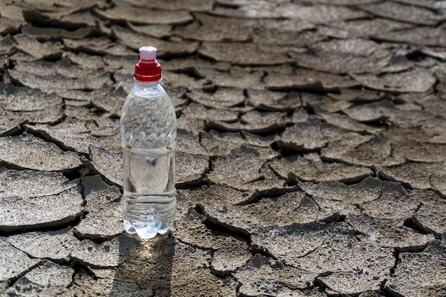 마른 금이 간 진흙 사막 한가운데에 깨끗한 식수가 든 플라스틱 병