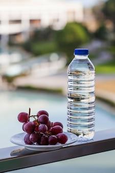 잘 익은 포도 옆에있는 식수와 플라스틱 병