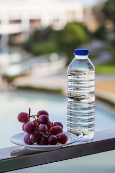 Plastic bottle with drinking water next to the ripe grapes