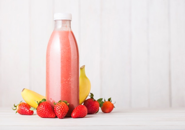 Plastic bottle with fresh summer berries smoothie on wooden table.strwberry and banana flavour.