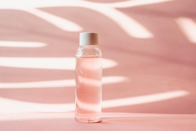 팜 리프의 열 대 그림자와 파스텔 배경에 핑크 장미 물 플라스틱 병. 투명한 토너와 토너로 피부를 보습하고 깨끗하게합니다. 기타 물 또는 클렌징 폼