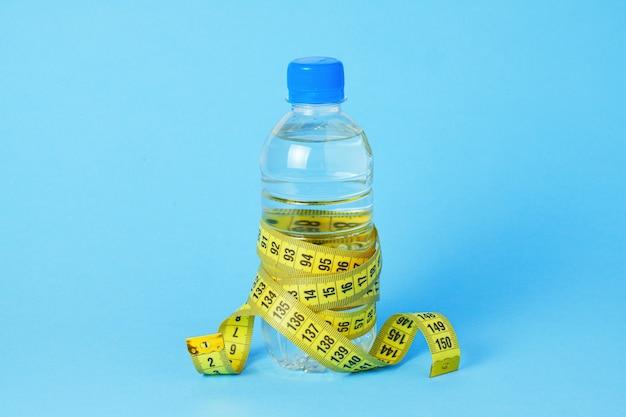 파란색 배경에 물과 측정 테이프가 있는 플라스틱 병.