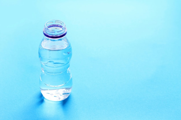 Plastic bottle with water on blue.