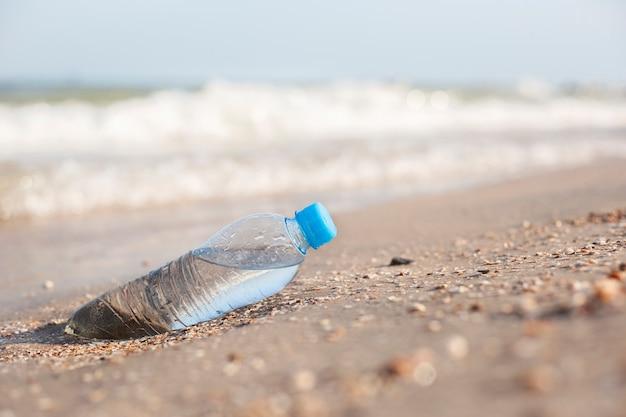 晴れた日の砂浜の背景に水が入ったペットボトル。