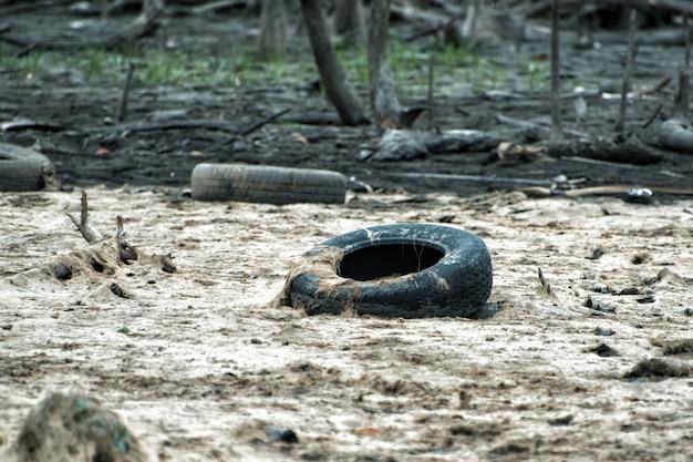 플라스틱 병과 더러운 물에 오래된 타이어. 환경 오염 문제.