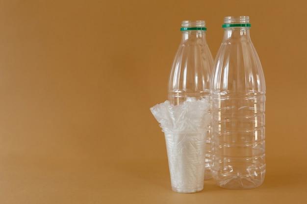 茶色の背景にガラスのペットボトルとビニール袋