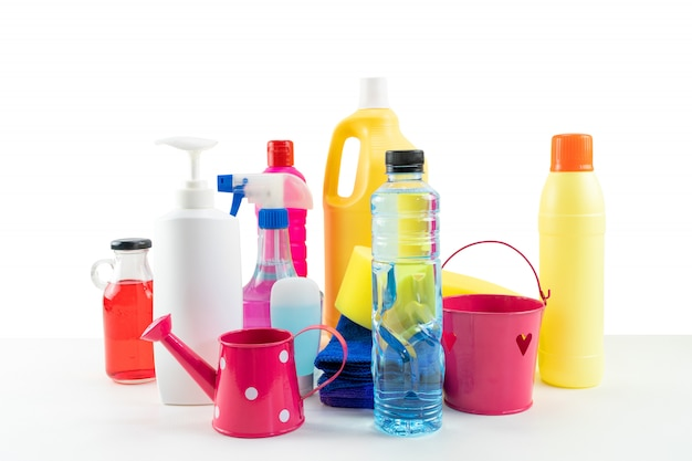 Plastic bottles of cleaning products set on white table.