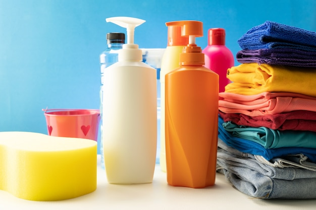 Plastic bottles of cleaning products with pile colorful clothes on table background.