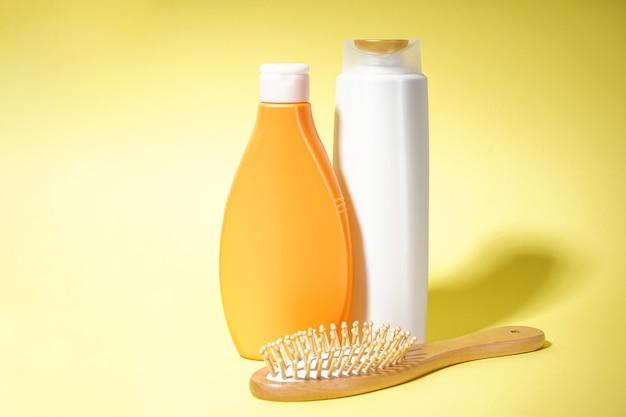 Пластиковые бутылки для ухода за телом и деревянная расческа на желтом фоне.