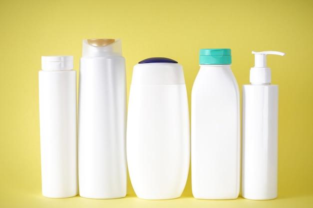 Пластиковые бутылки для ухода за телом и косметики на желтом фоне.
