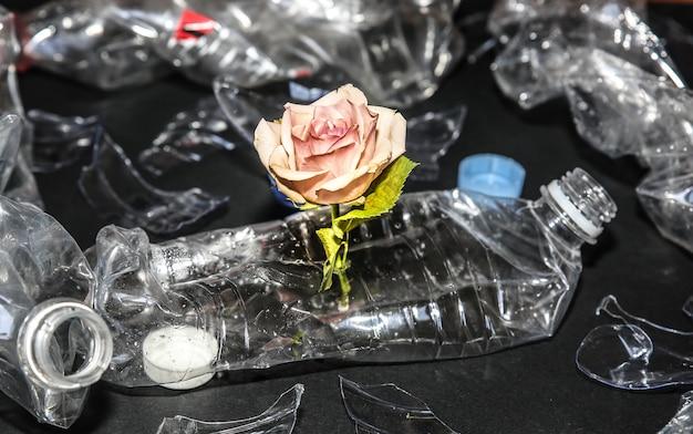 花と山に横たわっているペットボトル。環境汚染。生態学的災害。リサイクルの問題。