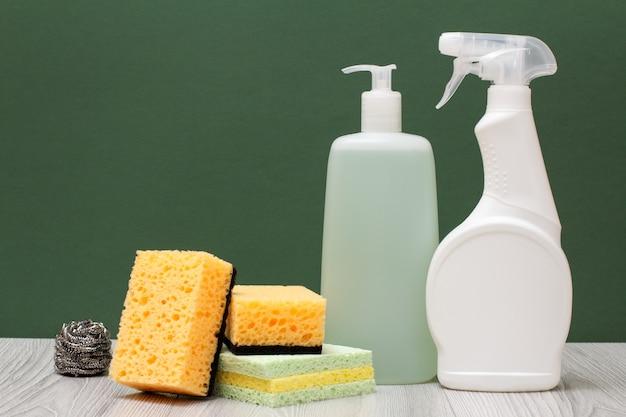 전자레인지와 스토브용 세제 플라스틱 병, 유리 및 타일 클리너, 녹색 배경에 스폰지. 세척 및 청소 개념입니다.