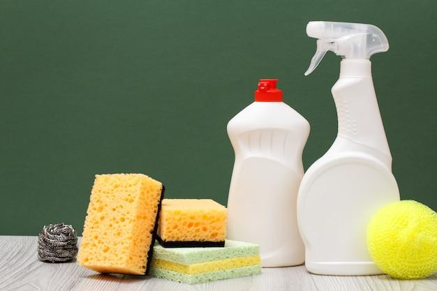 Пластиковые бутылки жидкости для мытья посуды, средства для чистки стекла и плитки, губки на зеленом фоне. концепция стирки и очистки.
