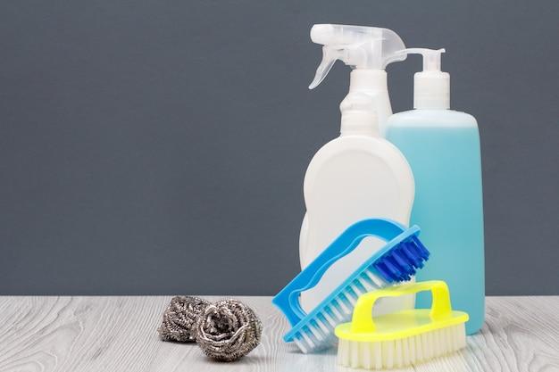 食器用洗剤のペットボトル、ガラスとタイルのクリーナー、灰色の背景にブラシと金属スポンジ。洗濯と掃除のコンセプト。