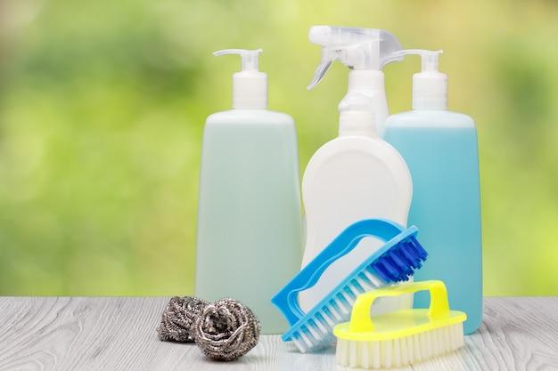 食器用洗剤のペットボトル、ガラスとタイルのクリーナー、電子レンジとストーブ用の洗剤、ぼやけた自然の背景にブラシと金属スポンジ。洗濯と掃除のコンセプト。