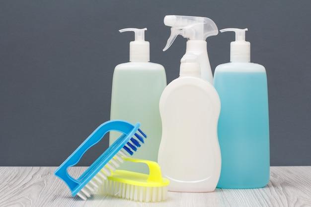 플라스틱 병, 식기세척액, 유리, 타일 클리너, 전자레인지와 스토브용 세제, 회색 배경의 브러시. 세척 및 청소 개념입니다.