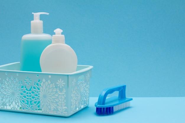 Пластиковые бутылки жидкости для мытья посуды, очиститель стекла и плитки в корзине и щетке на синем фоне. концепция стирки и очистки.