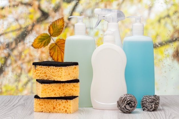 Пластиковые бутылки с жидкостью для мытья посуды, чистящим средством для плитки, моющим средством для микроволновых печей и плит, губками перед окном с каплями воды и осенними листьями. концепция стирки и очистки.