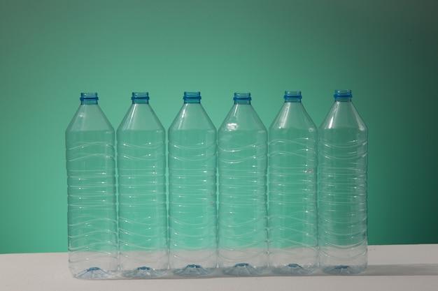 Пластиковые бутылки на синем фоне как символ экологических катастроф