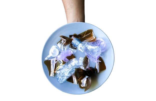 접시에 플라스틱 병입니다. 오염된 음식을 먹는 사람들. 환경 문제. 생태 재앙입니다. 재활용 문제. 나이프와 포크로 손입니다. 흰색 배경에 고립.