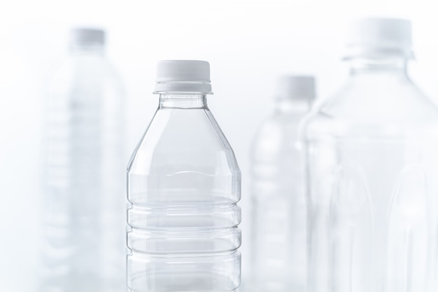 Plastic bottles in various shapes and sizes on white table and background