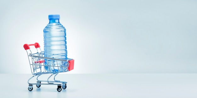 Plastic bottles of water in shop trolley on white background.