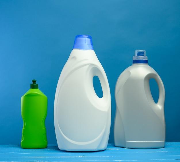 Пластиковые бутылки с моющими средствами на синем фоне, крупным планом