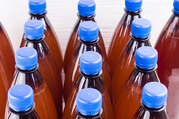 Пластиковые бутылки с домашним крафтовым пивом на белой поверхности эль или лагер из пилзнерского солода