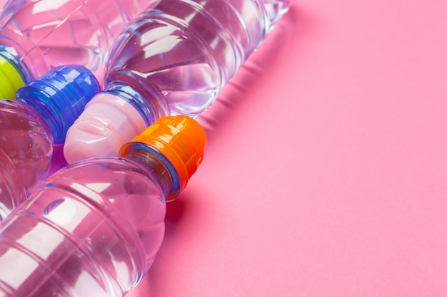 Plastic bottles with pure water on pink background, copyspace