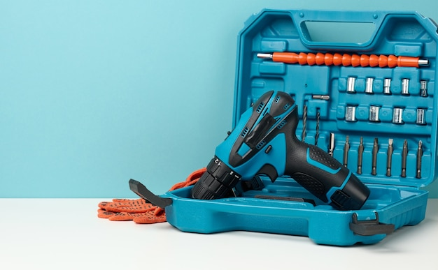 Plastic box with cordless drill and set of drills and screwdrivers on white background, copy space
