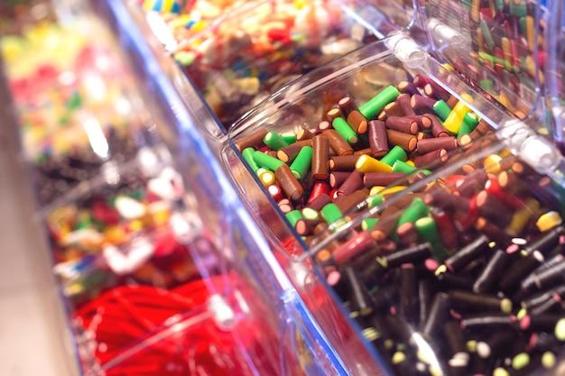 さまざまな種類のカラフルな甘い咀嚼キャンディーが入ったプラスチックの箱