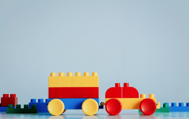 Plastic bricks car in yellow and red colors with trailer