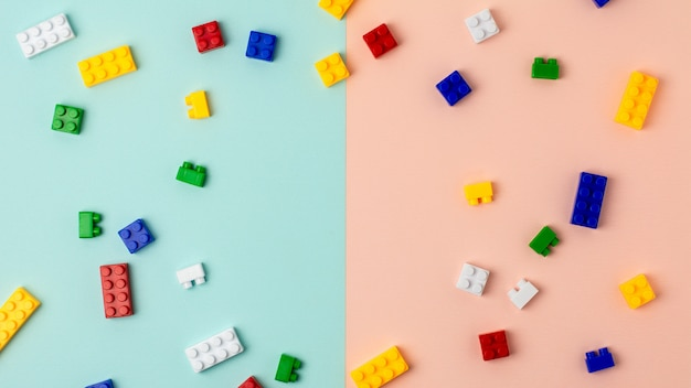Plastic building blocks on blue and pink background