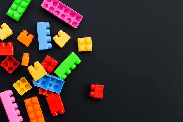 暗い壁にプラスチック製のビルディングブロック。