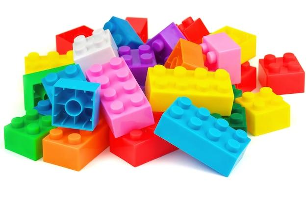 白い背景の上のプラスチック製の建物のカラフルなおもちゃのブロック