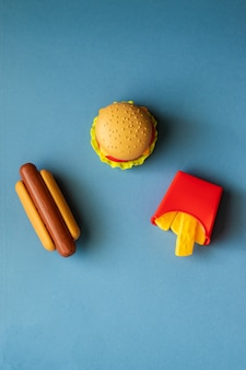 Plastic burger, salad, tomato, frying potatoes with a hot dog on a blue background