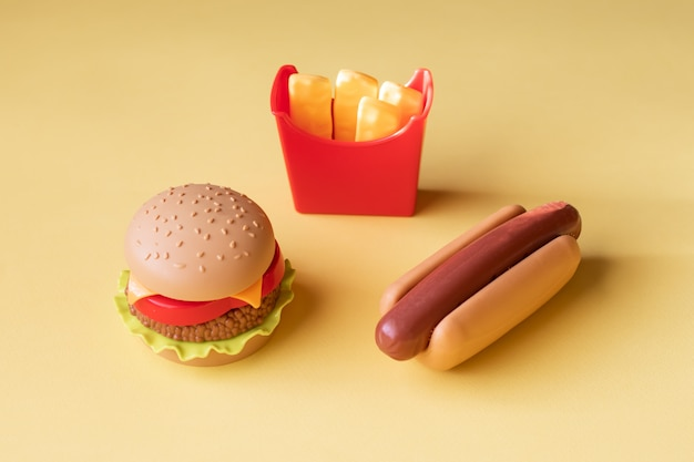 Plastic burger, salad, tomato, frying potatoes with a hot dog on a yellow background