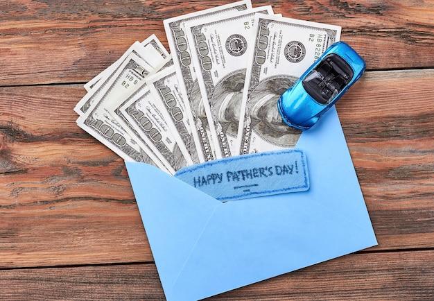 プラスチック製の車、グリーティングカード、お金。木の上の父の日カード。車を買うのに十分です。