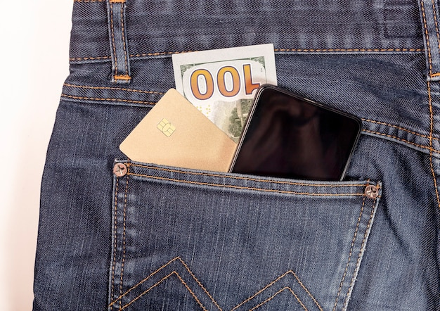 Plastic card, mobile phone and cash in dollars close up in jeans pocket.