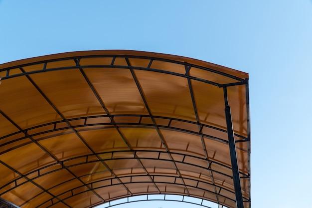 プラスチック製のカーポート。金属構造のポリカーボネート製の茶色の透明な屋根