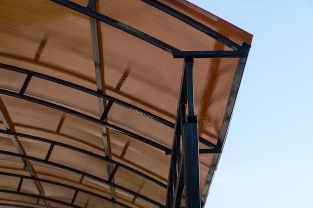 플라스틱 간이 차고. 금속 구조의 폴리카보네이트로 만든 갈색 투명 지붕