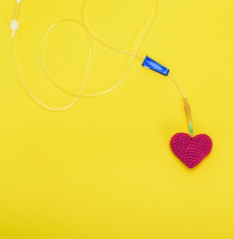 Plastic catheter with needle and red heart