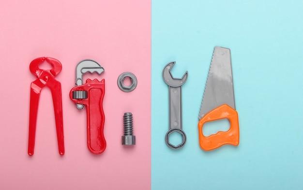 ピンクブルーのパステルカラーの背景にプラスチック製の子供用作業ツールキット。おもちゃ。上面図