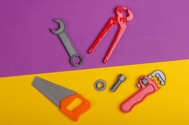 紫黄色の背景にプラスチック製の子供の作業ツールキット。おもちゃ。上面図
